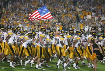 MIAMI - JANUARY 2:  The Iowa Hawkeyes take the field against USC as a team member holds the United States flag before the FedEx Orange Bowl on January 2, 2003 at Pro Player Stadium in Miami, Florida.  USC defeated Iowa 38-17.  (Photo by Eliot J. Schechter/Getty Images)